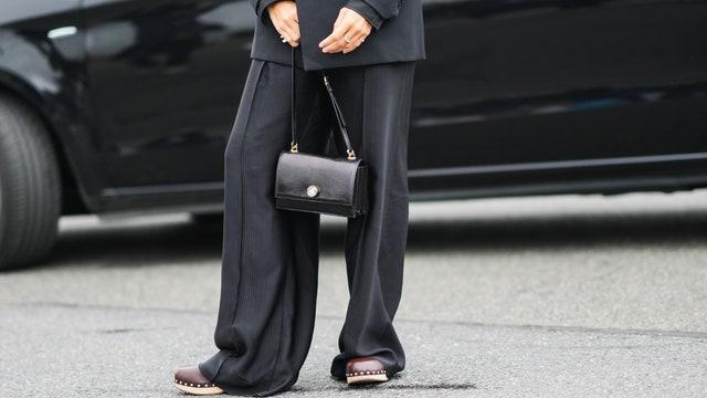 PARIS FRANCE  OCTOBER 02 A guest wears a black oversized blazer jacket high waist black large pants rings a black shiny...